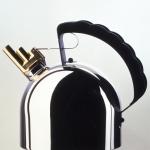 """Bollitore 9091 realizzato per Alessi nel 1983:  dispone di un fischietto melodico in ottone con due tubi sintonizzati sulle note """"mi"""" e """"si"""""""