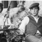 1972:  American actor Al Pacino (right) sits with Italian actor Franco Citti holding a rifle at an outdoor table in director Francis Ford Coppola's film, 'The Godfather'. Pacino rests his leg on a chair.  (Photo by Paramount Pictures/Getty Images)